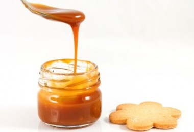Pouring caramel in a small jar with a spoon with a cookie next to it, horizontal shot